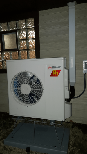 Schaumburg, IL Mitsubishi ductless mini split heat pump with stand to keep Hyper Heat system out of the snow during winter cold weather heating.