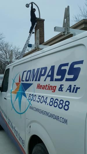 Compass Heating and Air Conditioning, Inc. technician installing a chimney liner as part of a high efficiency furnace installation, in Elk Grove, IL.
