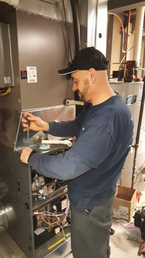 Compass Heating and Air Conditioning, Inc. technician installing an Amana AMVC97 modulating furnace, in Streamwood,IL.