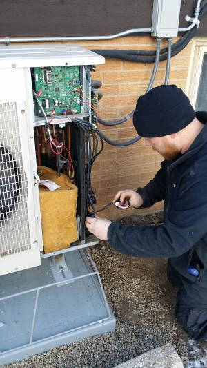 Compass Heating and Air Conditioning, Inc. technician performing a repair on a Mitsubishi ductless air conditioning system, in Sleepy Hollow, IL.