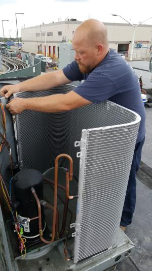 Compass Heating and Air Conditioning, Inc. technician replacing a micro-channel condensing coil on a Lennox Commercial rooftop unit RTU, in Rosemont, IL.