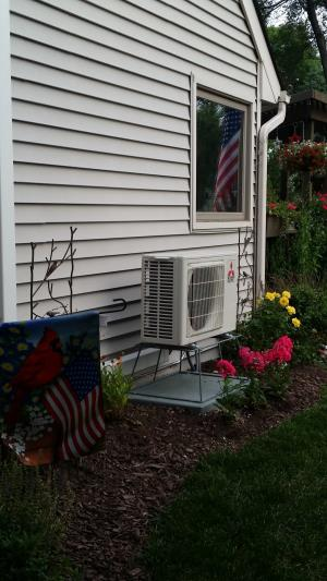 Mitsubishi Hyper Heat H2i heat pump, installed in Schaumburg, IL with patriotic flag reflection in window. July 4th fourth celebration and ulitimate VRF variable capacity comfort.