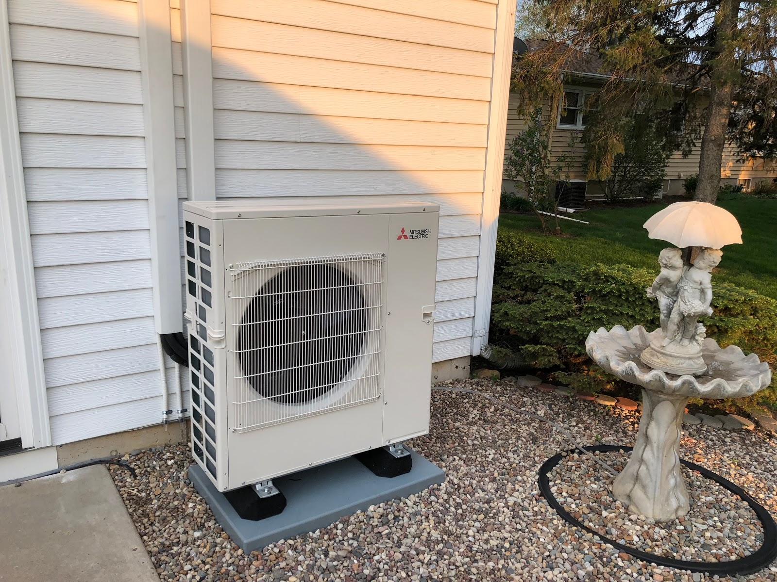 Example of an outdoor heat pump condenser installed outside a split level home.